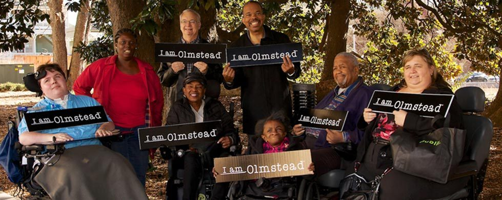 Diverse Group of People with Disabilities Holding I am Olmstead Signs
